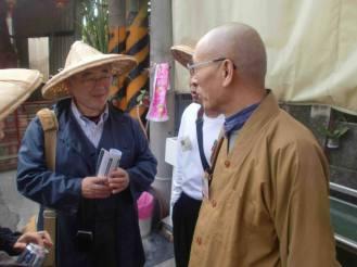 Rev. Okochi speaks with a Buddhist monk on the walk in Dalin