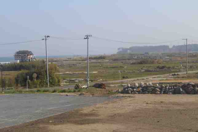 The barren tsunami ravaged plain of Namie with the reactors in the distance